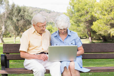80s adult: Elderly couple using laptop in the park sitting on bench LANG_EVOIMAGES