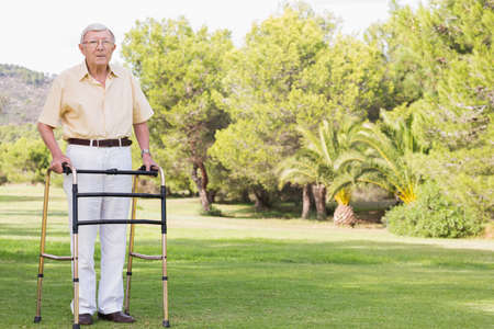 80s adult: Portrait of old man using zimmer frame in the park