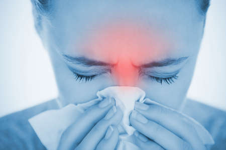 eyes looking down: Woman blowing her nose with highlighted red sinus pain in blue tint