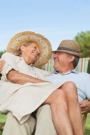 lap: Happy woman sitting on lap of partner sitting in deck chair outdoors on a sunny day LANG_EVOIMAGES