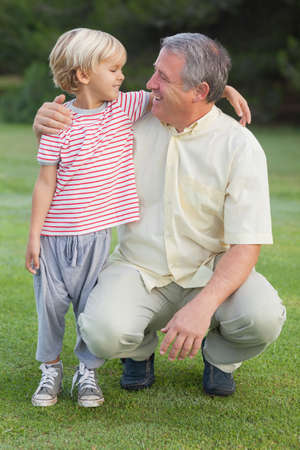 crouching: Grandfather crouching beside grandson looking at each other in a grassy area