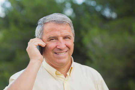 grey haired: Grey haired man using his mobile portrait outdoors in the countryside