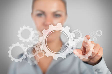 grey background: Businesswoman pressing wheels and cogs graphic on grey background LANG_EVOIMAGES