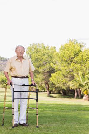 80s adult: Portrait of elderly man using zimmer frame in the park LANG_EVOIMAGES