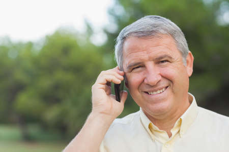 grey haired: Grey haired man on the phone outdoors in the countryside