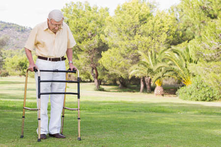 convalescence: Elderly man using zimmer frame to walk in the park