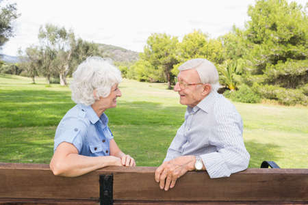80s adult: Elderly couple chatting together on park bench in the park LANG_EVOIMAGES