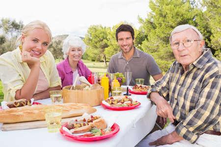 the offspring: Retrato de la sonrisa de la familia con hijos adultos sentado en la mesa de picnic en el parque LANG_EVOIMAGES