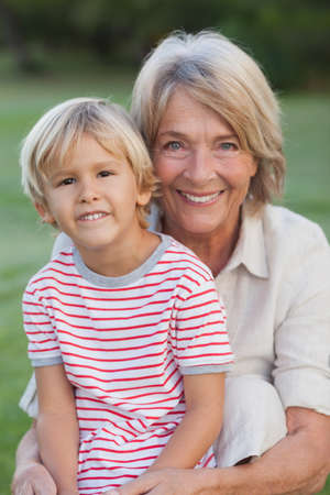 grandmother and grandson: Portrait of smiling grandmother with grandson in a park