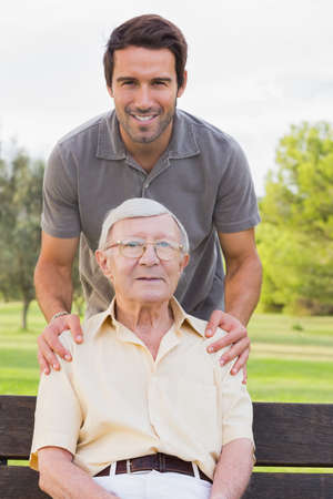 senior adult man: Portrait of elderly father sitting on park bench with adult son