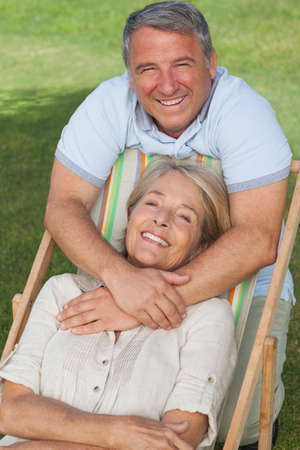 lawn chair: Portrait of older couple with woman in deck chair smiling on the lawn