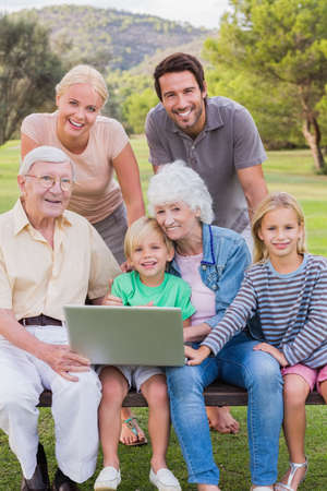 multigeneration: Portrait of happy multigeneration family in the park using laptop with some sitting on park bench LANG_EVOIMAGES