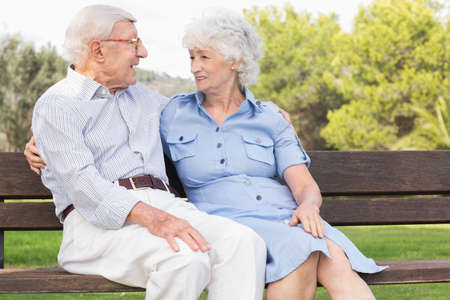 80s adult: Elderly couple sitting on bench talking in the park LANG_EVOIMAGES