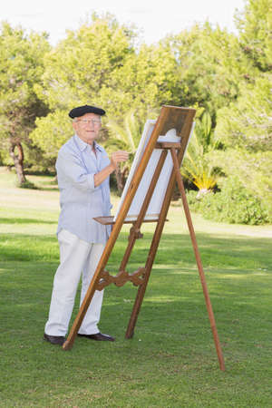 80s adult: Portrait of elderly smiling man painting in park