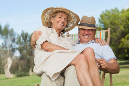 lap: Smiling woman sitting on lap of partner sitting in deck chair on a sunny day