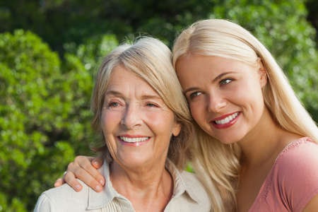 adult offspring: Smiling mother with adult daughter posing outdoors in countryside