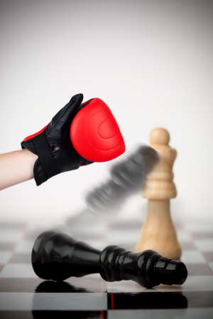 knocked over: Hand of boxer knocking over black chess piece on chessboard