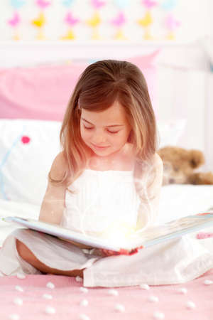 storybook: Little girl reading a storybook sitting on her bed