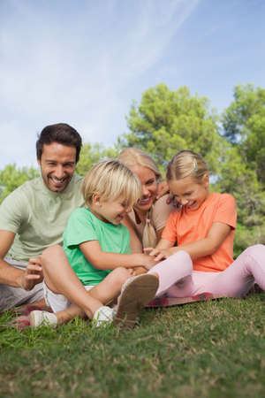 messing: Happy family sitting on picnic blanket and messing together in the park
