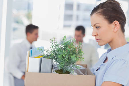 let go: Annoyed businesswoman leaving office after being let go holding box of her things