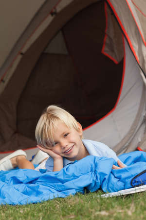 campsite: Cute little boy lying on sleeping bag in front of tent at the campsite