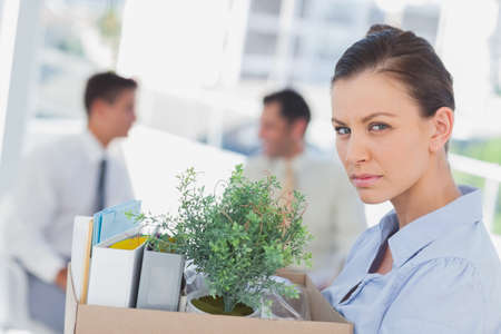 let go: Unhappy businesswoman leaving office after being let go and looking at camera LANG_EVOIMAGES