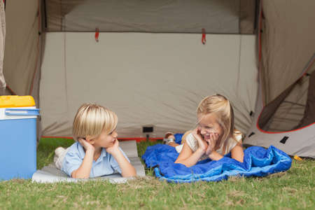 campsite: Brother and sister talking on the campsite under the tent LANG_EVOIMAGES