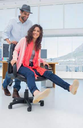 swivel: Creative business colleagues having fun on a swivel chair in a modern office
