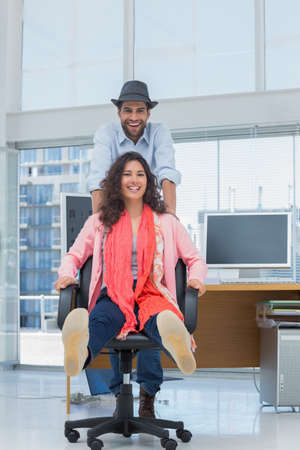 swivel chairs: Photo editors having fun on a swivel chair in a modern office LANG_EVOIMAGES