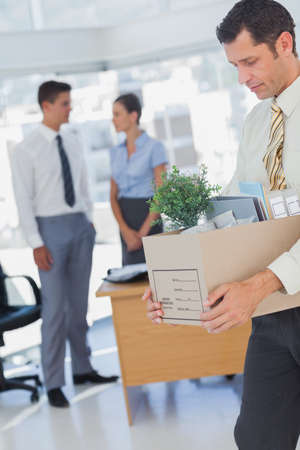 well laid: Businessman leaving office after being laid off carrying box of his things LANG_EVOIMAGES