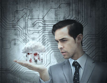 hand held computer: Concentrated businessman holding a cloud for cloud computing with circuit board on the background
