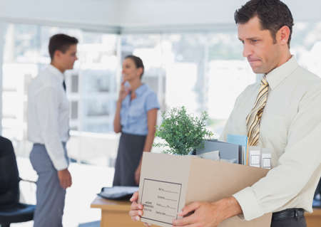 well laid: Businessman leaving office after being fired holding box of his things
