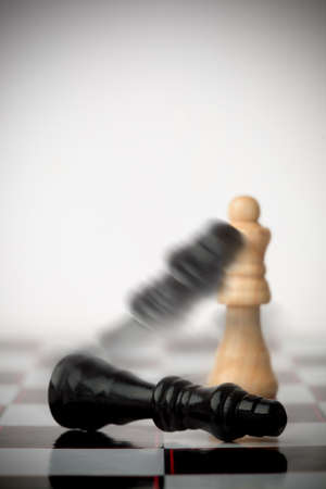 knocked over: Black chess pieces falling over on chessboard LANG_EVOIMAGES