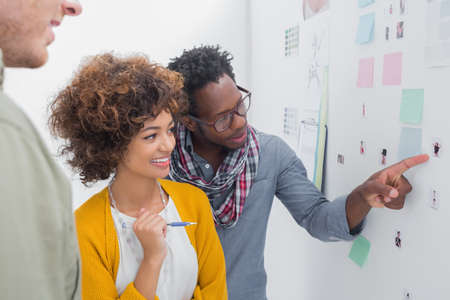 black professional: Team of designers pointing at a photo stick up on a wall