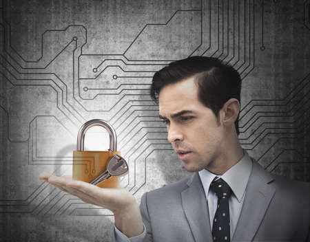 concentrated: Concentrated businessman holding a padlock over circuit board background