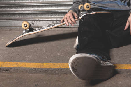 sitting on the ground: Skater sitting on ground with board against metal shutters