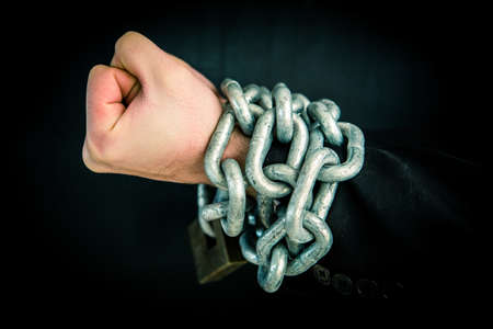 constricted: Hand wrapped in chain and lock on black background