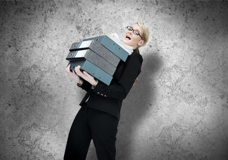 work load: Businesswoman struggling with work load on grey wall backgroud