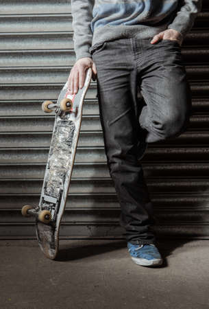 leaning on the truck: Skater standing against metal shutters holding his board up