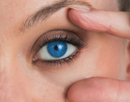blue eye: Woman stretching her blue eye LANG_EVOIMAGES