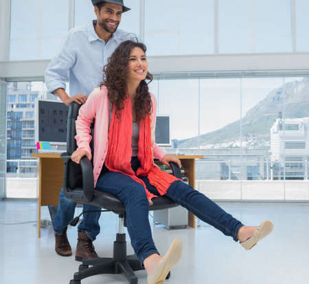 swivel chairs: Creative business colleagues having fun on an office chair in a modern office