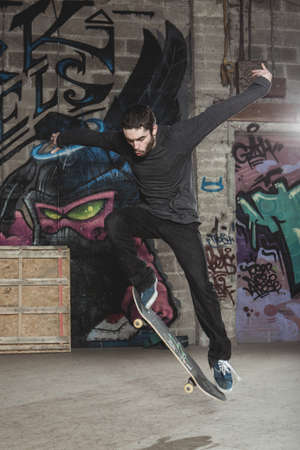 impressive: Skater doing impressive backside half cab 180 trick in the skate park with graffiti walls LANG_EVOIMAGES