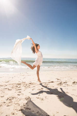 sarong: Pretty young woman jumping with sarong on the beach
