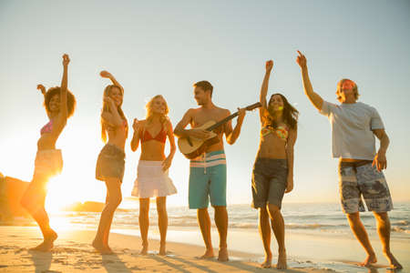sunny beach: Group of friends having a party and playing guitar on the beach