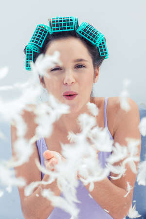 hair roller: Attractive woman wearing pajamas and blowing feathers LANG_EVOIMAGES