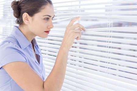 nosey: Businesswoman peeking through venetian blind in an office LANG_EVOIMAGES