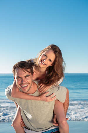 light hair: Man giving a piggy back to his girlfriend during summer on the beach