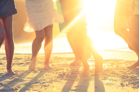 short wave: Close up of legs of people on the beach in front of the sunset