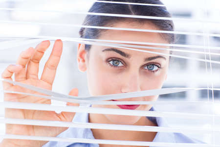 nosey: Delighted businesswoman peeking through a venetian blind in a bright office