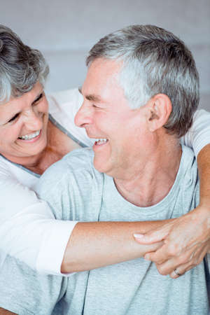 nightwear: Retired couple laughing together while they are wearing nightwear